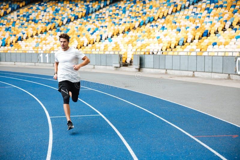 Esprinter joven que corre en pista del atletismo fotos de archivo libres de regalías