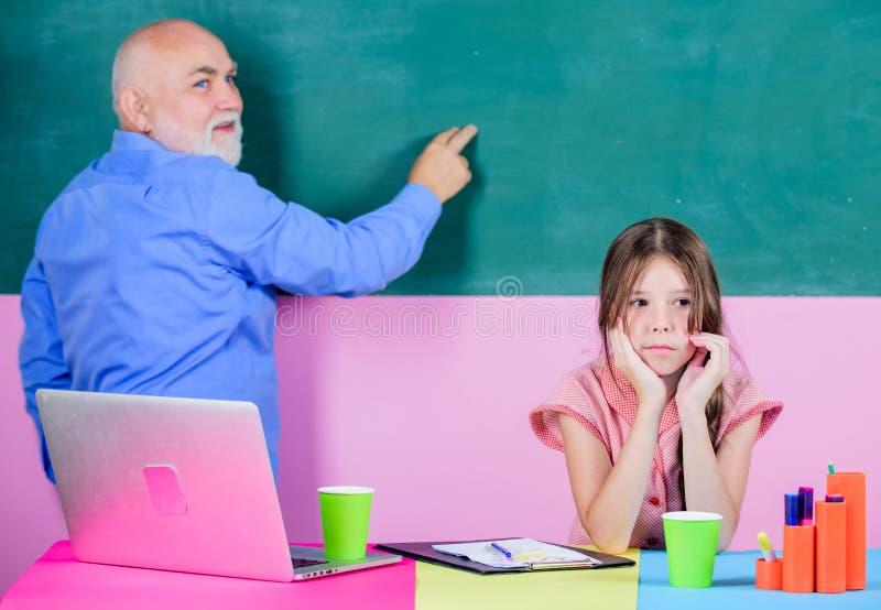 Esprit rebelle nouvelle technologie dans l'étude aide mûre de professeur instruire la fille peu de fille avec l'étude de tuteur d photos libres de droits