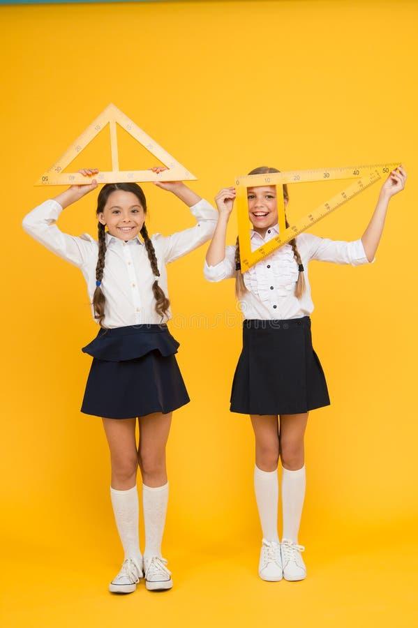 Esprits lumineux Enfants dans l'uniforme au mur jaune Amiti? et fraternit? les petites filles heureuses étudient des mathématique photos stock