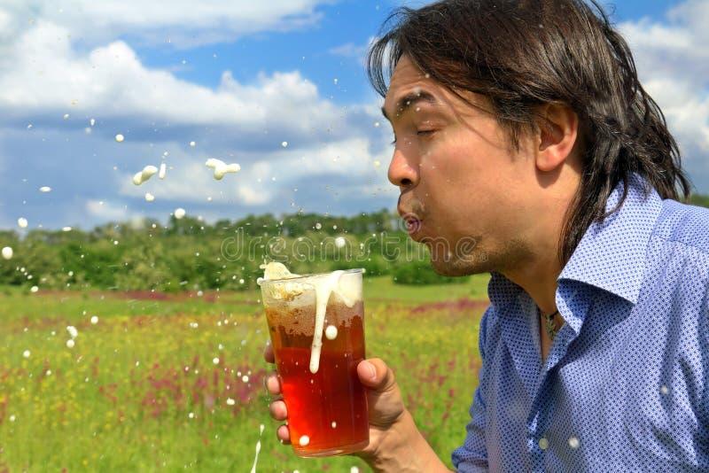 Espuma ausente de sopro da cerveja do homem novo imagens de stock