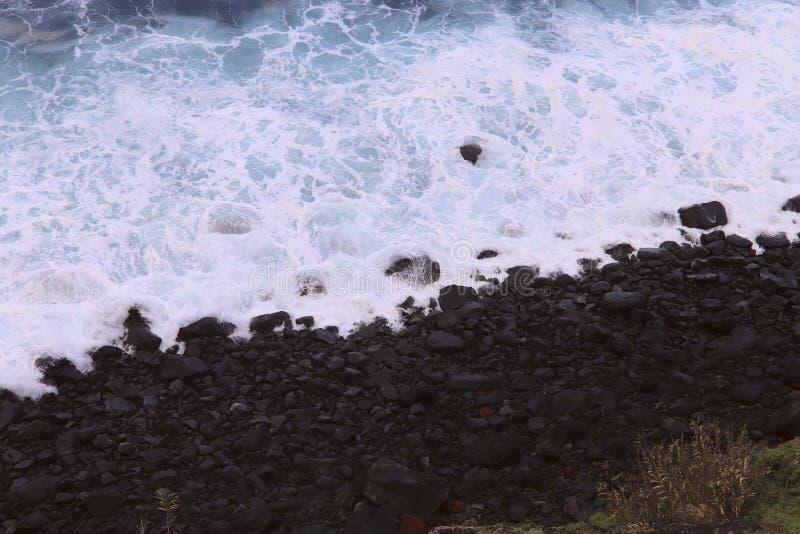 Espuma blanca del agua del océano cerca de la costa con las piedras oscuras Costa de la isla de Madeira imagen de archivo