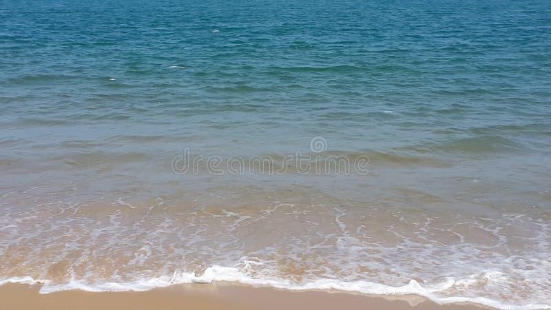 Espuma blanca en la costa, el agua azul del océano y las pequeñas ondas en la playa - Lagos, Nigeria - tema de las vacaciones y d imagen de archivo libre de regalías