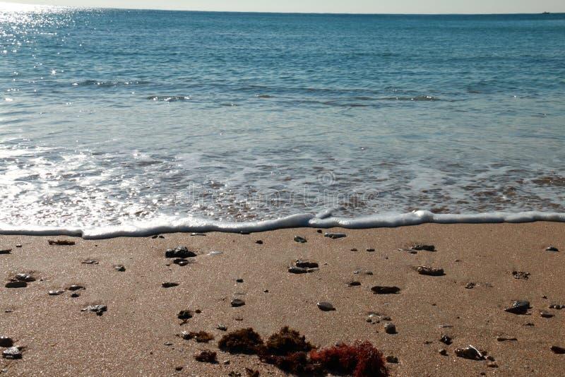 A espuma das ondas de um mar calmo que alcança a areia da praia fotografia de stock