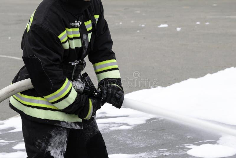 Espuma de alimentação de um bombeiro handheld, fogo - extinguir a espuma voa fora do tronco, que mantém o bombeiro no combate fotografia de stock royalty free