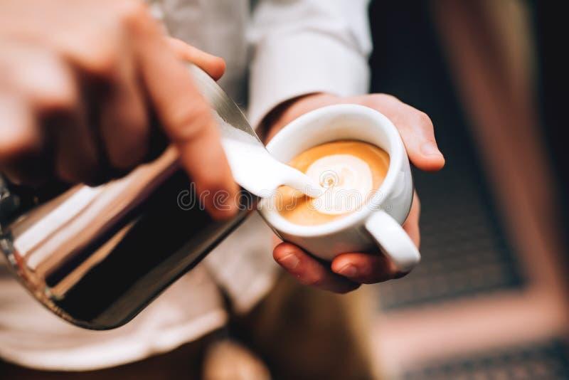 Espuma de derramamento do latte de Barista sobre o café, o café e a criação de um cappuccino perfeito imagens de stock royalty free