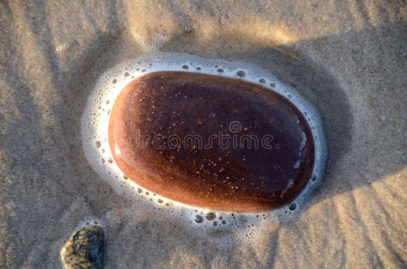 Espuma de la piedra y del mar en la playa imagen de archivo libre de regalías