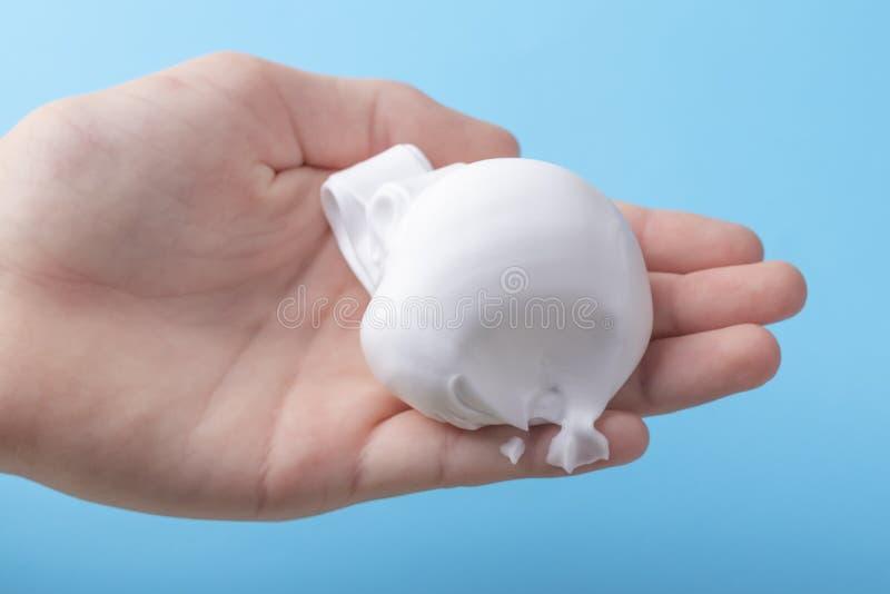 Espuma de rapagem branca na mão de um adolescente em um fundo brilhante azul fotos de stock royalty free