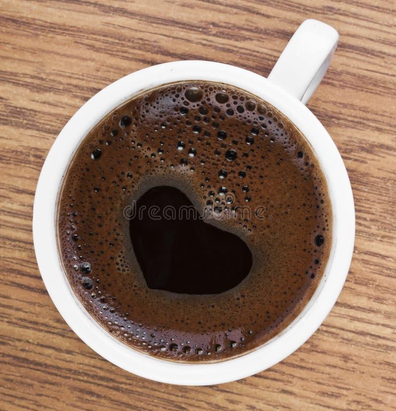 Espuma del café de la forma del corazón sobre el vidrio blanco imagen de archivo