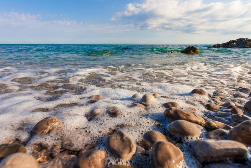 Espuma del mar en la playa pedregosa fotografía de archivo libre de regalías