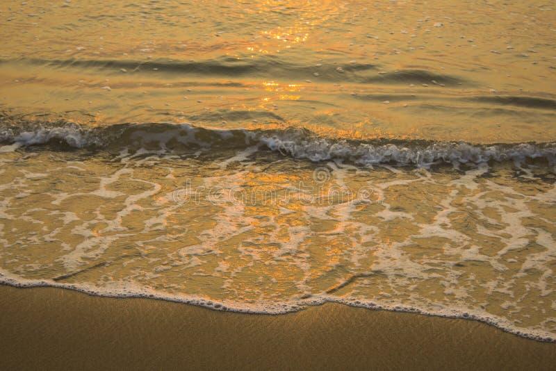 Espuma do close-up de ondas do mar em um Sandy Beach amarelo com os remendos de nivelar a noite fotos de stock royalty free