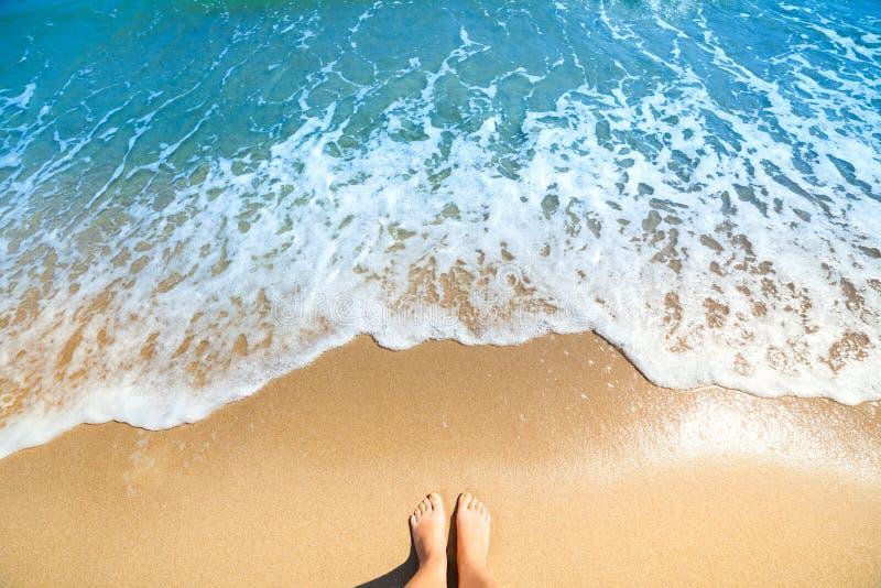 A espuma do mar, as ondas e os pés despidos em uma areia encalham fotografia de stock royalty free