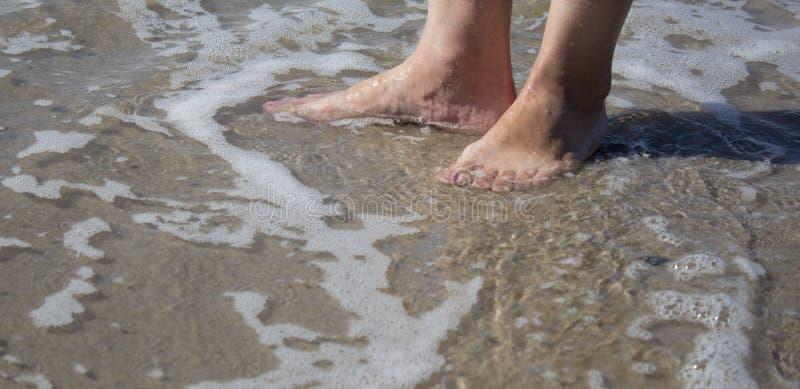 A espuma do mar, as ondas e os pés despidos em uma areia encalham Os feriados, relaxam fotografia de stock