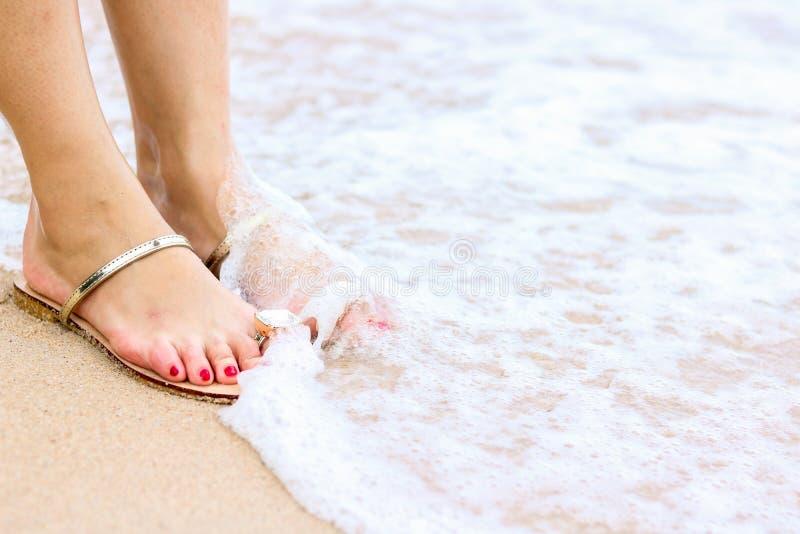 A espuma do mar, as ondas e os p?s despidos em uma areia encalham Os feriados, relaxam imagens de stock royalty free