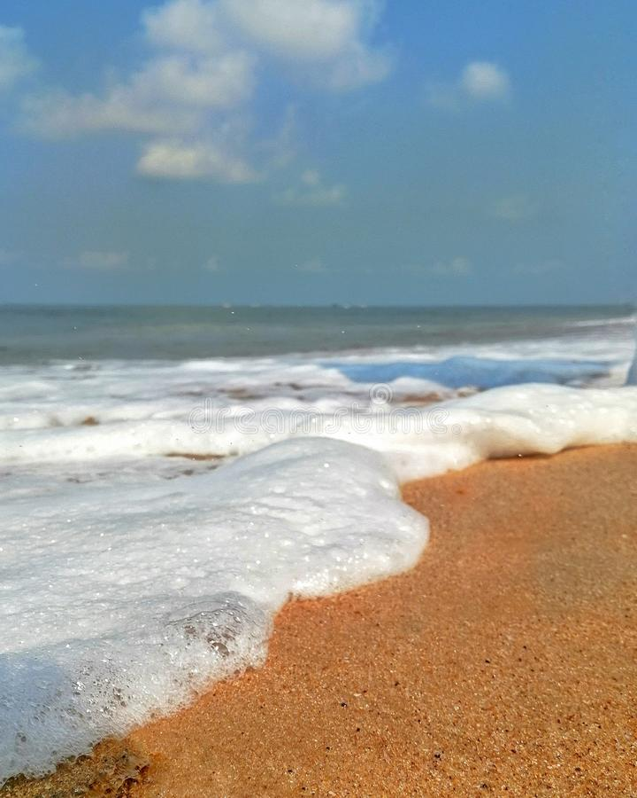 A espuma e as bolhas lavadas pelas ondas delicadas na praia de Goa Calungute fotografia de stock royalty free