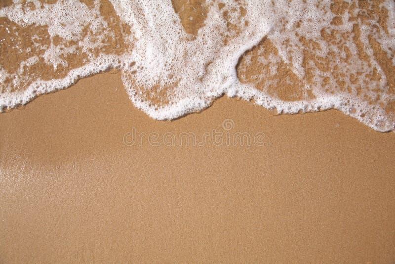 Espuma na areia imagens de stock