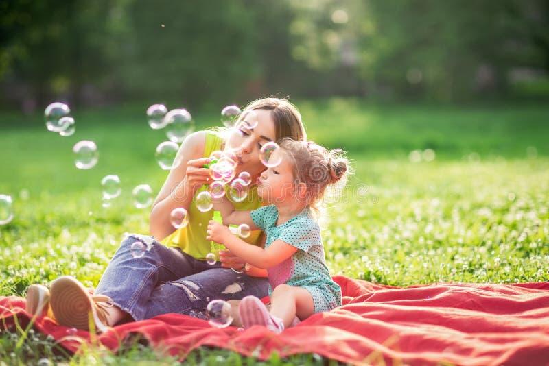 """Espuma nova da sopa dos sopros da mãe e da criança do †feliz da infância """"e para fazer bolhas foto de stock"""