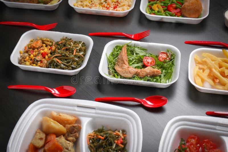 Espumam os recipientes plásticos com alimento delicioso no fundo escuro imagem de stock royalty free