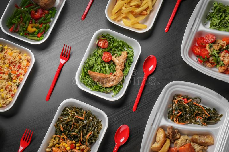 Espumam os recipientes plásticos com alimento delicioso no fundo escuro fotos de stock