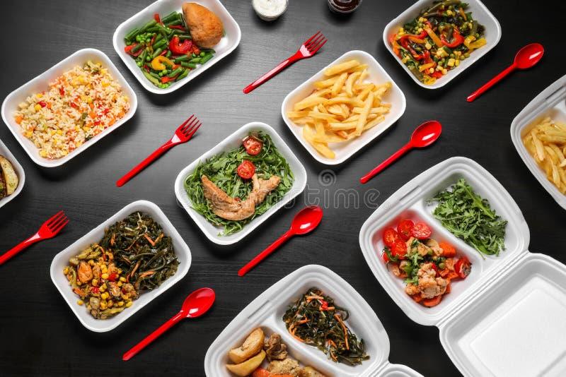 Espumam os recipientes plásticos com alimento delicioso no fundo escuro foto de stock royalty free