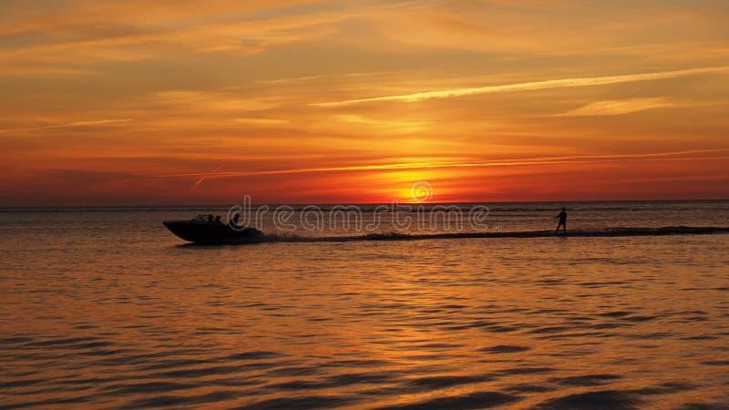 Esquí acuático en el mar en la puesta del sol anaranjada imagen de archivo