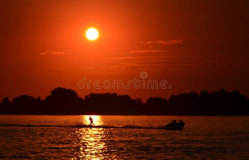 Esquí acuático en el río en la puesta del sol imagenes de archivo