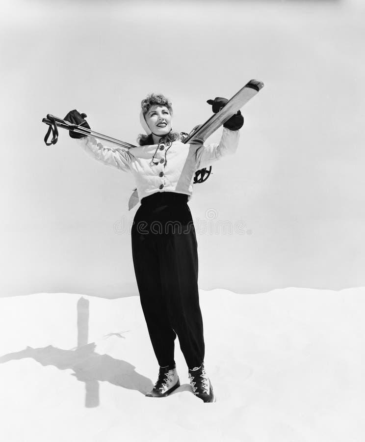 Esquí de la mujer joven y polo de esquí que llevan en sus hombros (todas las personas representadas no son vivas más largo y ning fotos de archivo libres de regalías