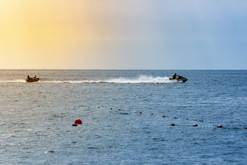 Esquí del jet del estilo libre de la impulsión del hombre en la puesta del sol del verano Fondo del verano fotografía de archivo libre de regalías