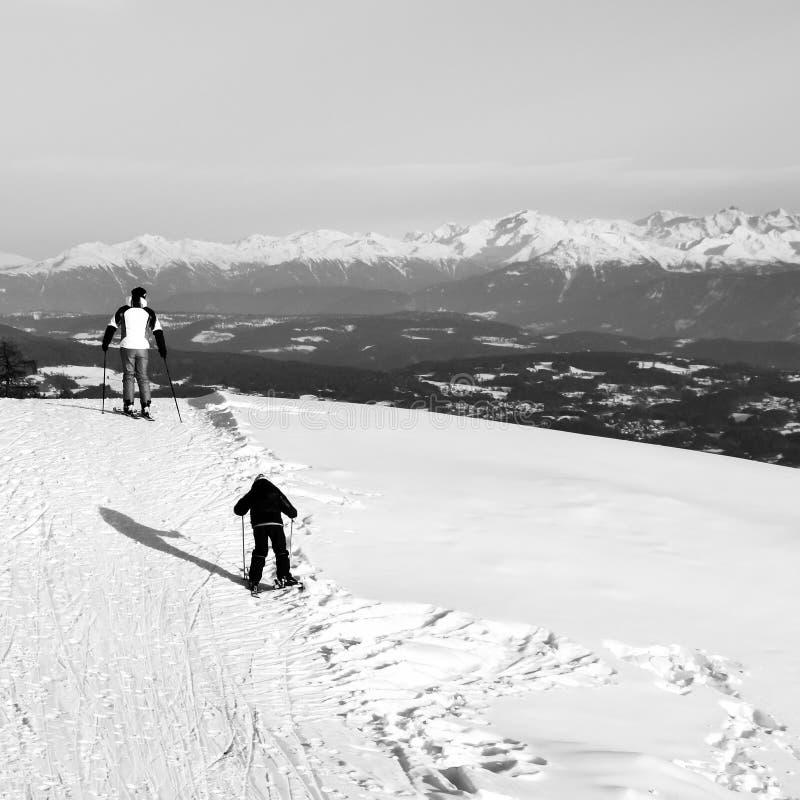 Esquí del padre y del hijo en las cuestas nevosas de las montañas imagenes de archivo