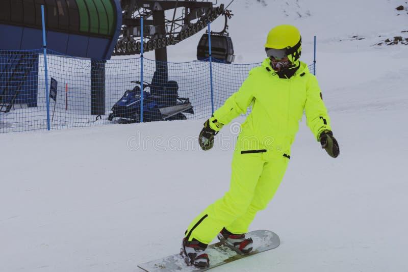 Esquí del Snowboarder en el traje amarillo brillante, guardapolvos fotografía de archivo libre de regalías