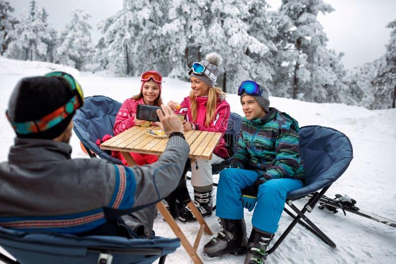 Esquí, diversión del invierno - engendre tomar la imagen de la familia en nieve fotos de archivo libres de regalías