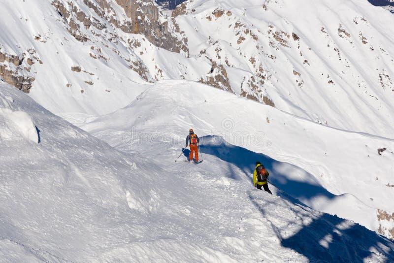 Esquí, esquiador, pase gratis en la nieve fresca del polvo - hombre con subidas de los esquís al top fotografía de archivo