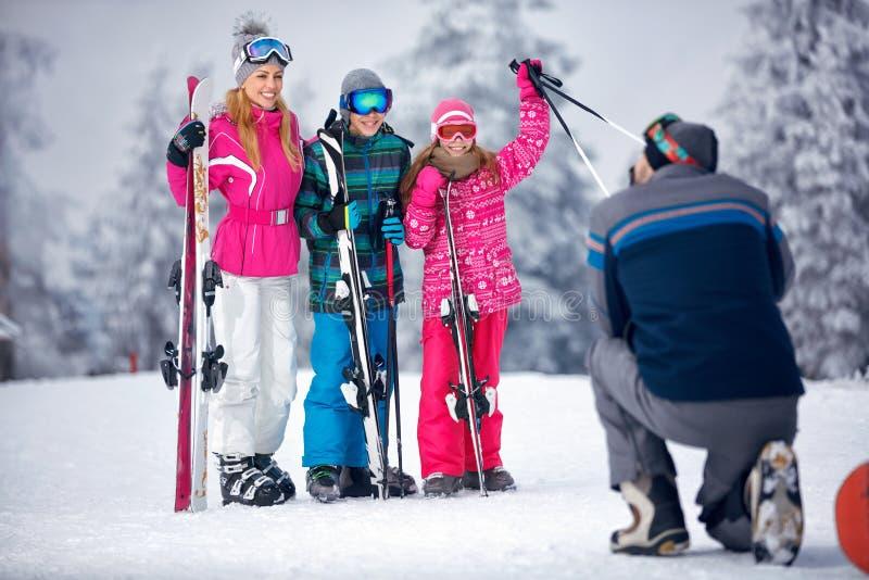 Esquí, sol de la nieve y diversión - engendre tomar la imagen de la familia en nieve foto de archivo