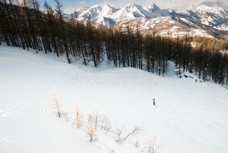 Esquí solamente en un valle con el bosque y cumbres y nubes de la montaña foto de archivo