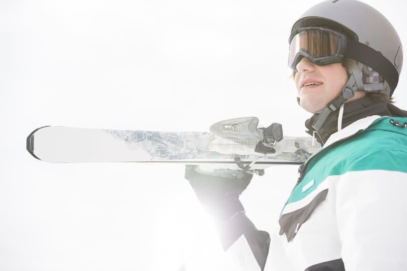 Esquís que llevan sonrientes del hombre joven contra el cielo claro foto de archivo