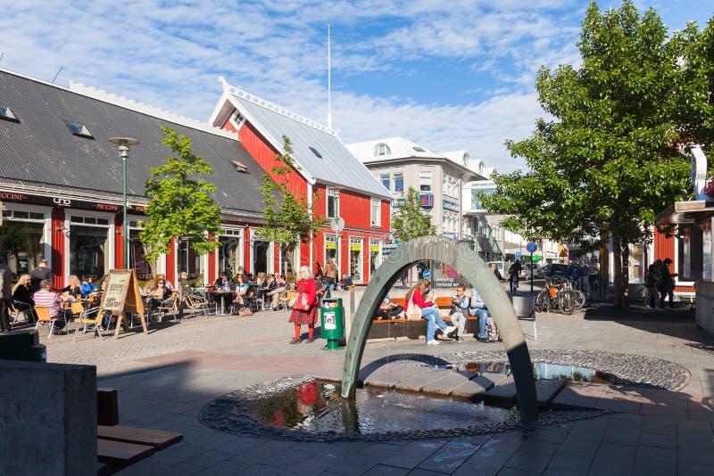 Esquadre em Reykjavik com uma fonte e uns cafés exteriores foto de stock
