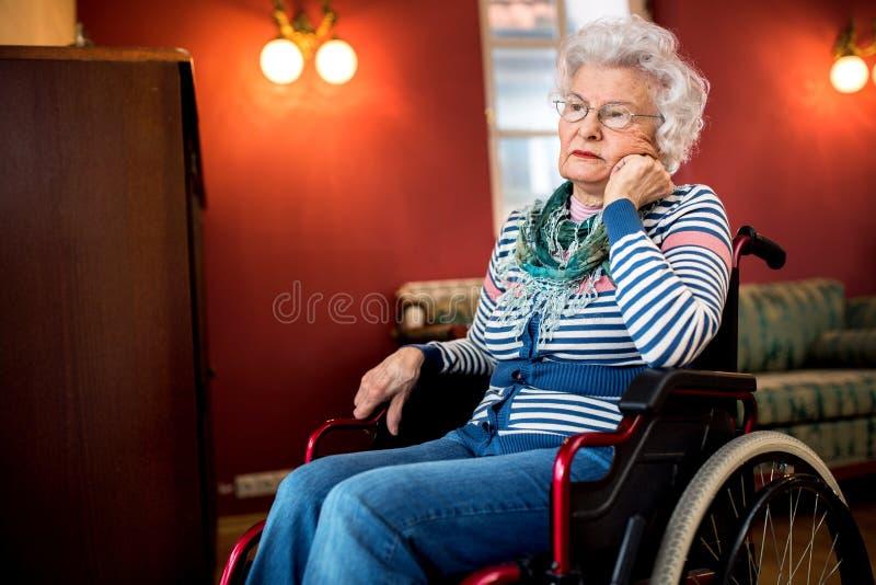 Esquecido pela família, mulher superior triste na cadeira de rodas imagem de stock