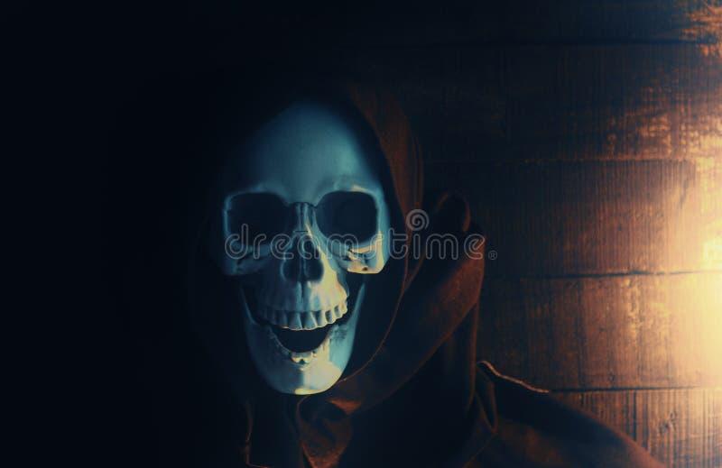Esqueleto asustadizo del fantasma del traje de Halloween que lleva una capa encapuchada/a un parca con el cr?neo en capilla negra foto de archivo
