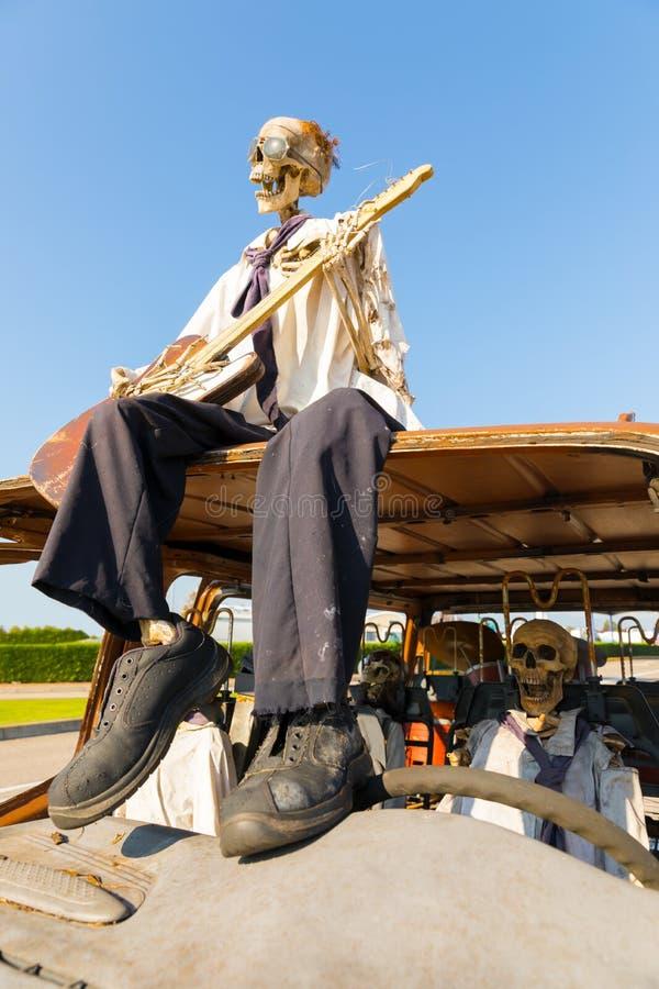 Esqueleto com a guitarra sobre o carro imagens de stock royalty free