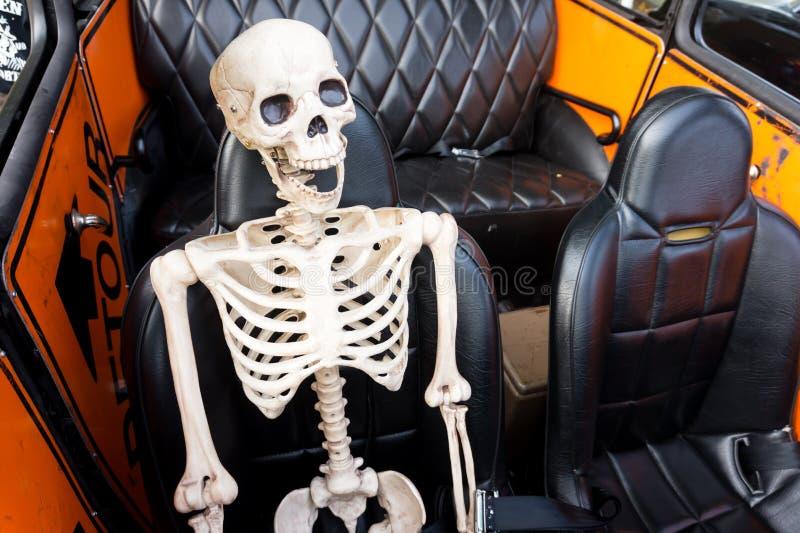 Esqueleto de risa en un coche fotos de archivo