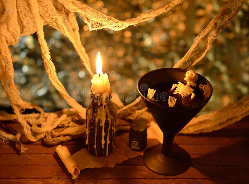 Esqueleto en winecup con la vela imagen de archivo
