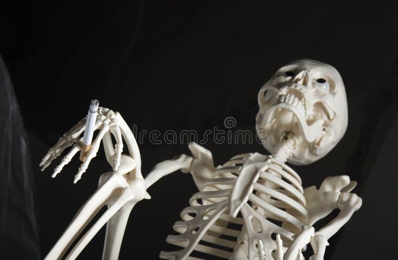 Esqueleto humano con el cigarrillo fotografía de archivo libre de regalías