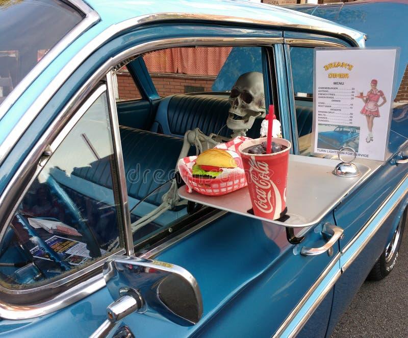Esqueleto humano em um carro do vintage em um jantar do cinema ao ar livre imagens de stock royalty free