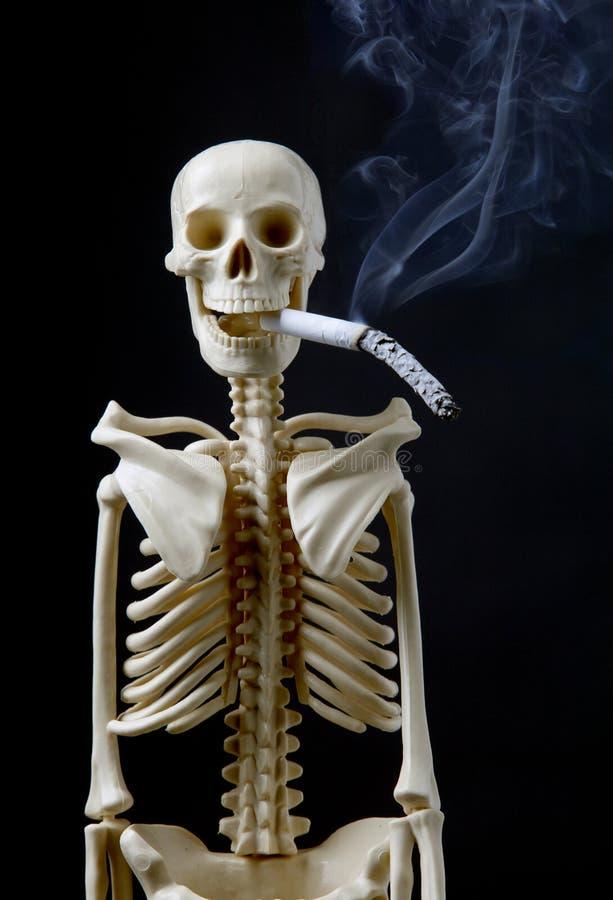 Esqueleto parado del concepto que fuma con el cigarrillo foto de archivo
