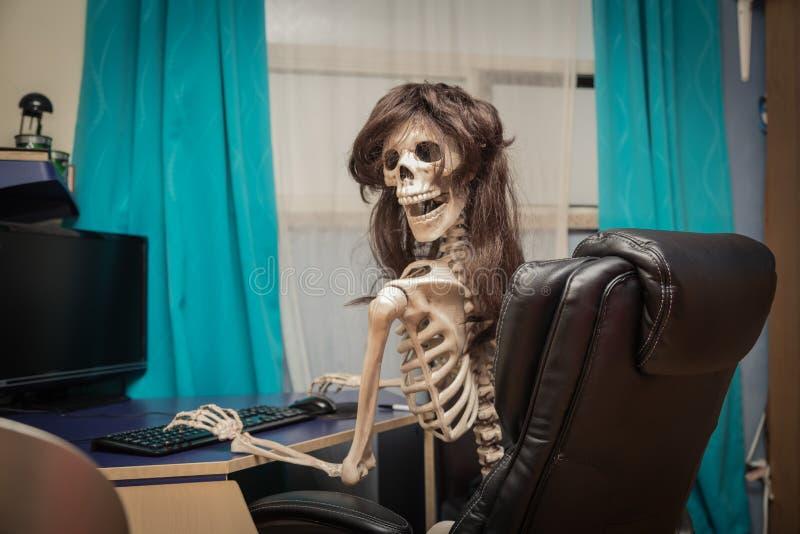 esqueleto sonriente en una peluca que se sienta en sitio en la silla de cuero negra detrás de la mesa foto de archivo libre de regalías