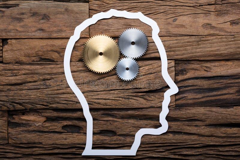 Esquema de papel de la cabeza del ` s del hombre de negocios con los engranajes metálicos en la tabla foto de archivo
