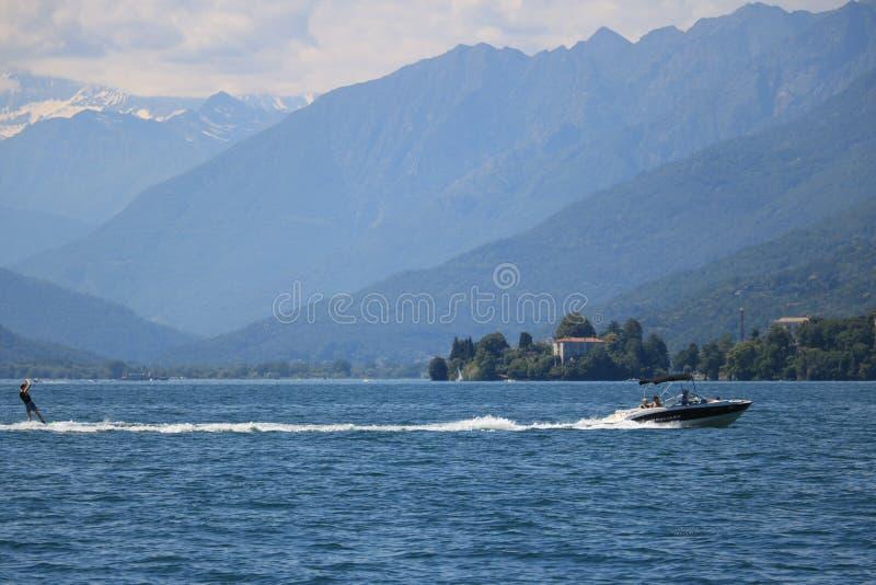 Esqui aquático no lago Maggiore Um barco a motor puxa um esquiador no foto de stock royalty free