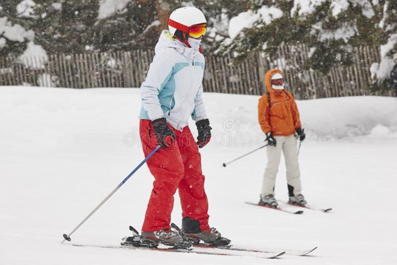 Esqui da mulher sob a neve Esporte de inverno Inclinação do esqui imagem de stock royalty free