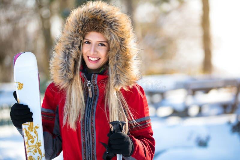 Esquiador bonito da mulher com esqui e polos foto de stock royalty free