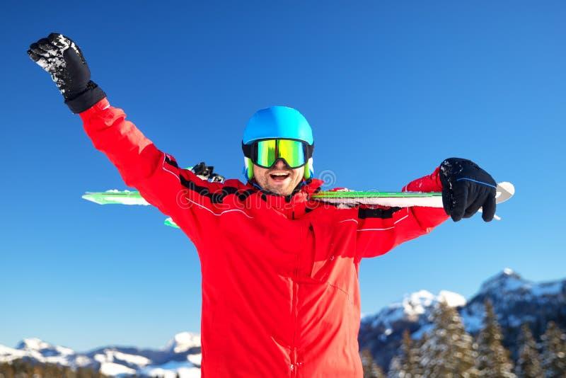 Esquiador caucasiano atrativo novo com o esqui nos cumes suíços prontos para esquiar imagem de stock royalty free