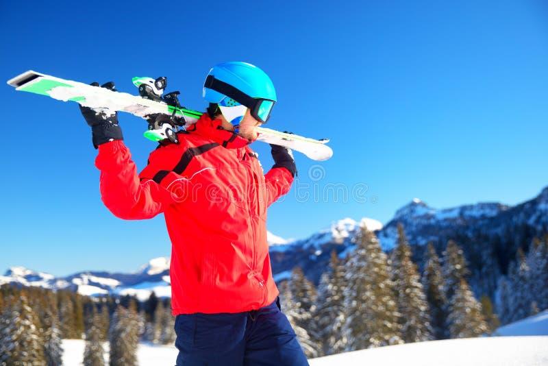 Esquiador caucasiano atrativo novo com o esqui nos cumes suíços prontos para esquiar imagens de stock